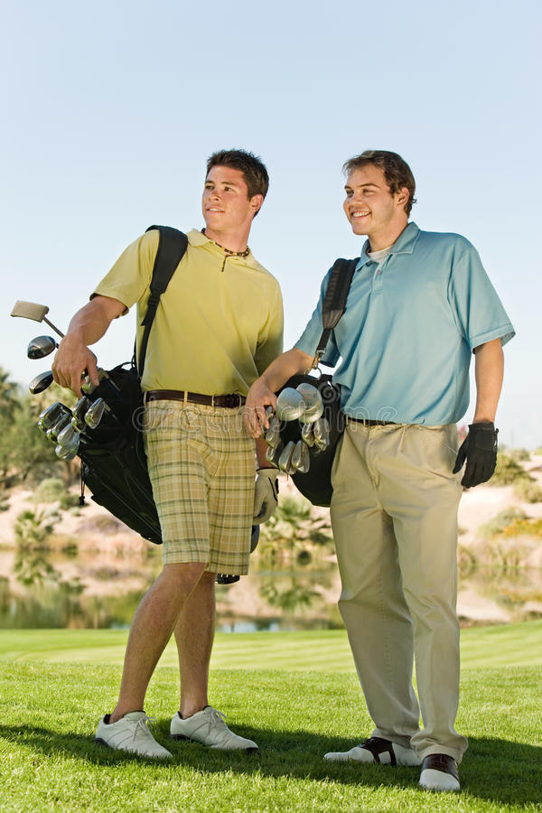 Golfeurs masculins portant des sacs de golf photo libre de droits