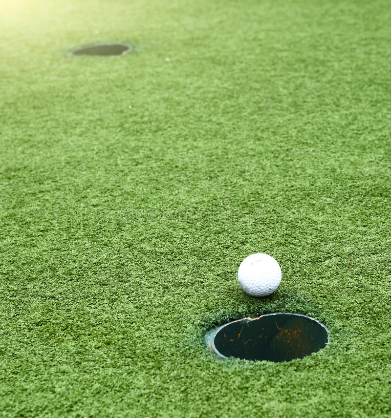 Golffälthål med bollen som går till fällan royaltyfria bilder