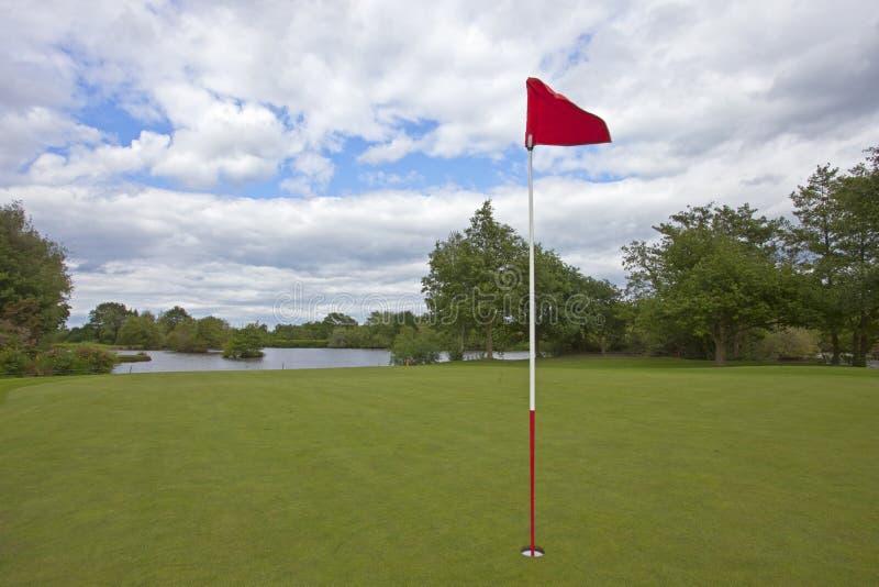 Golfgräsplan med den röda golfflaggan arkivbilder