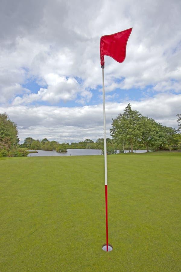 Golfgräsplan med den röda golfflaggan royaltyfri bild