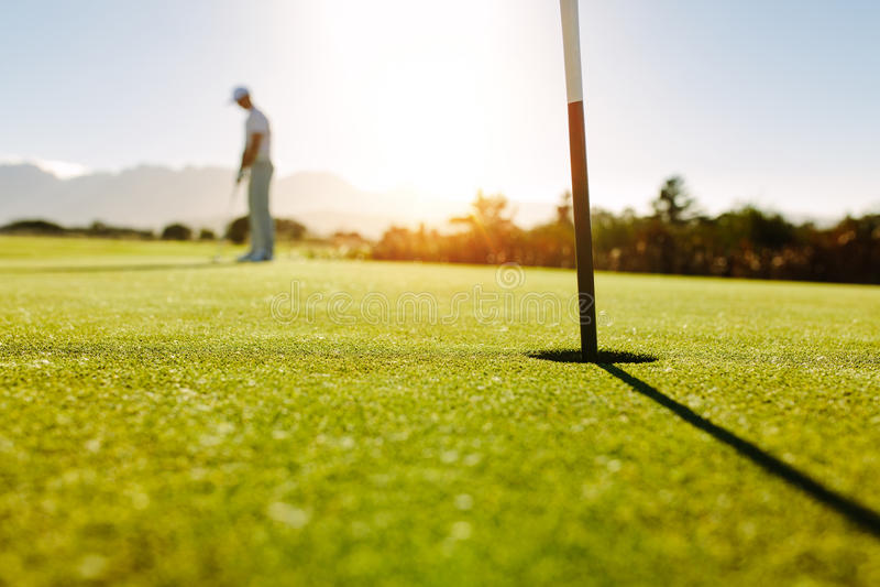 Golfhål och flagga i det gröna fältet med golfaren arkivfoton