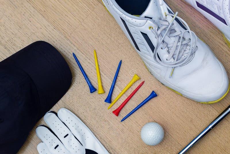 Golfhjälpmedel som skor, utslagsplatser, handske, boll och locket royaltyfri foto