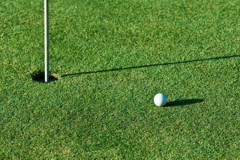 Golfing. A golf ball a short putt away from the hole with the flag still in it royalty free stock photo