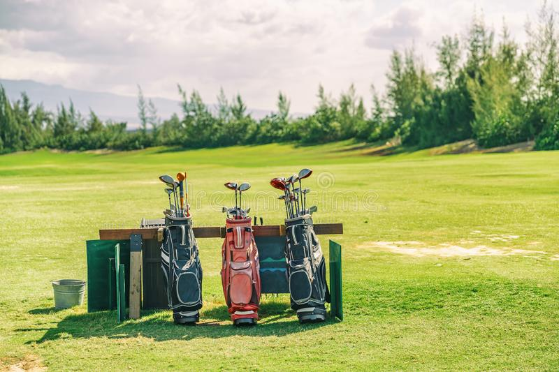 Golfing bags with clubs on golf course green grass royalty free stock photos