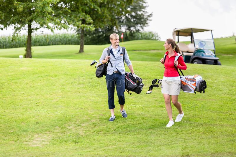 Golfing couple carrying their bags royalty free stock photography