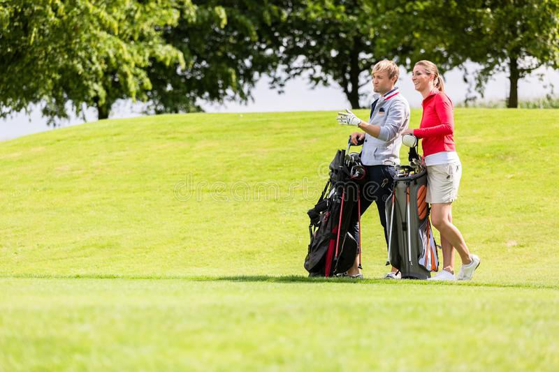 Golfing couple at golf field stock image