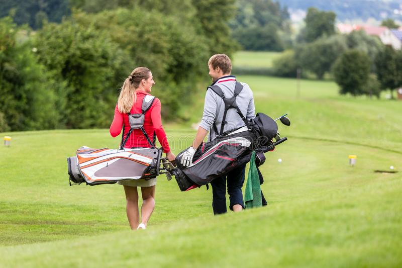 Golfing couple walking and chatting on golf course stock photos