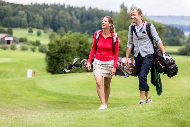 Golfing couple walking together on golf course stock photo