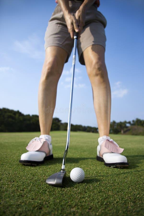 Golfing della femmina adulta immagine stock