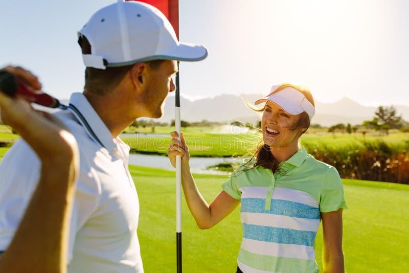 Golfingspaar op zetten groen bij de golfcursus royalty-vrije stock afbeeldingen