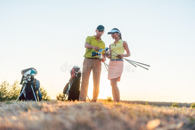 Golfinstruktör som undervisar en ung kvinna hur man använder olika golfklubbar royaltyfri foto
