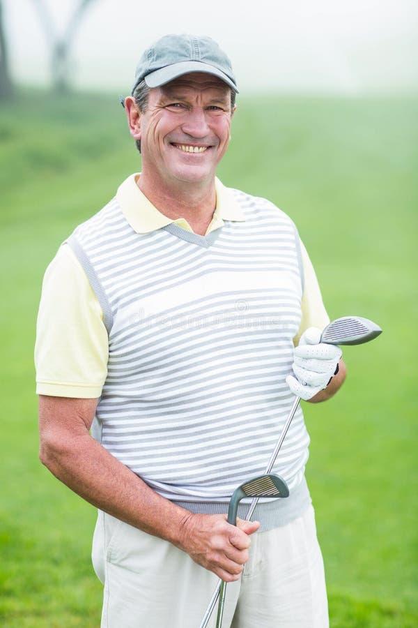 Golfista alegre que sonríe en la cámara que detiene a su club fotos de archivo