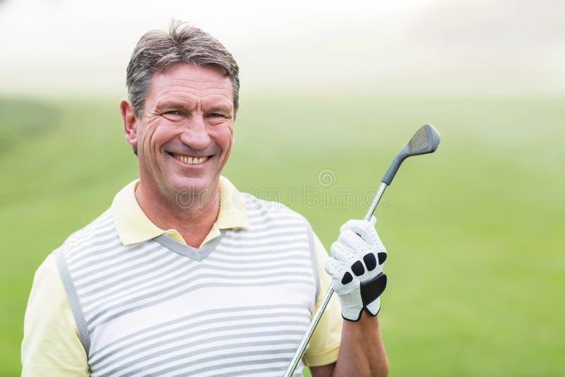 Golfista alegre que sonríe en la cámara que detiene a su club imagenes de archivo