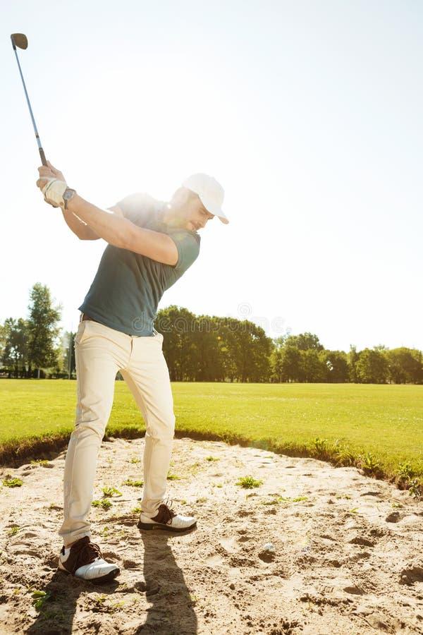 Golfista alrededor para golpear la bola fuera de una arcón de la arena fotos de archivo