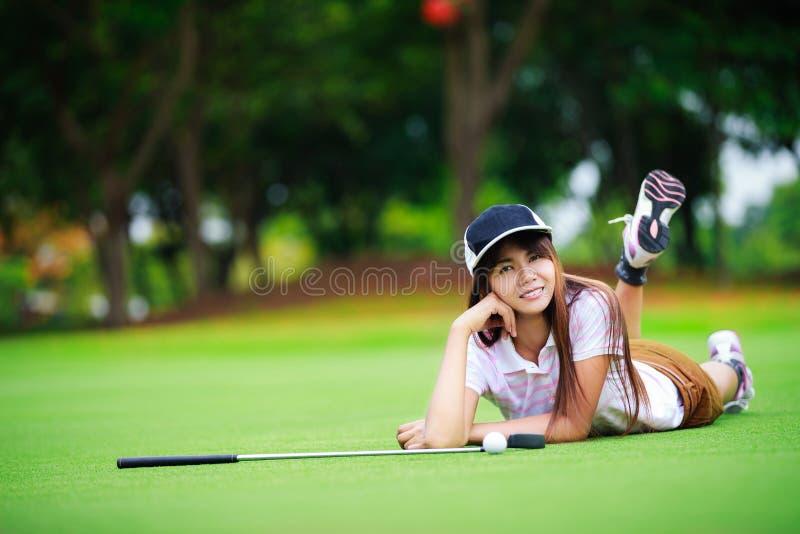 Golfista asiático que pone en la hierba verde imagenes de archivo