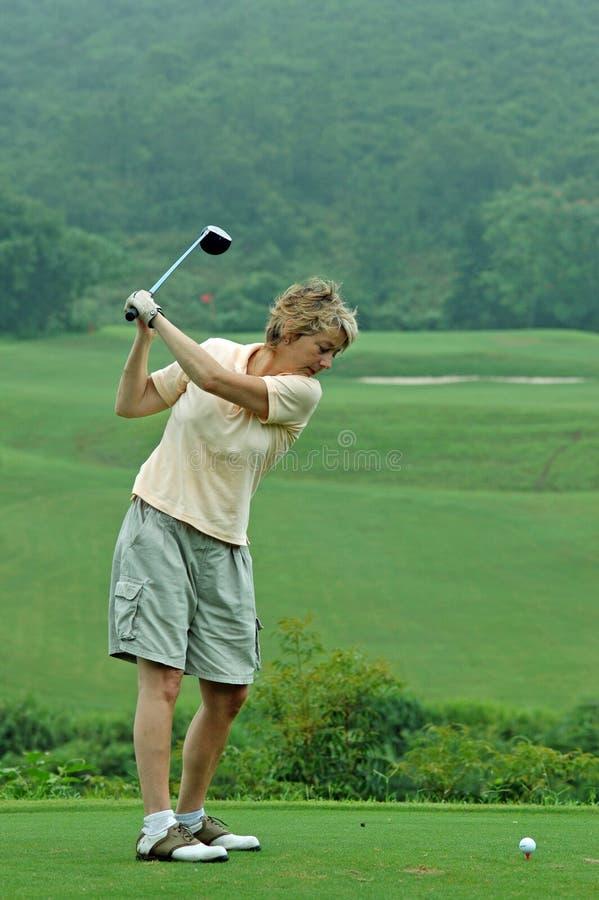 Golfista de la mujer alrededor para juntar con te de/mecanismo impulsor sobre el espacio abierto foto de archivo libre de regalías