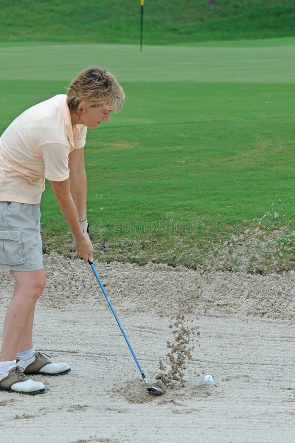 Golfista de la mujer en una arcón de la arena fotos de archivo