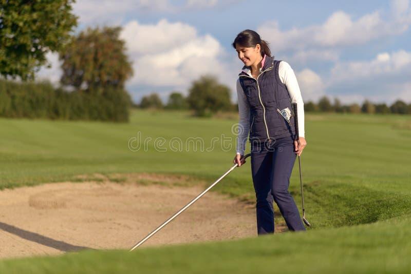 Golfista de la mujer que rastrilla una arcón de la arena imagen de archivo
