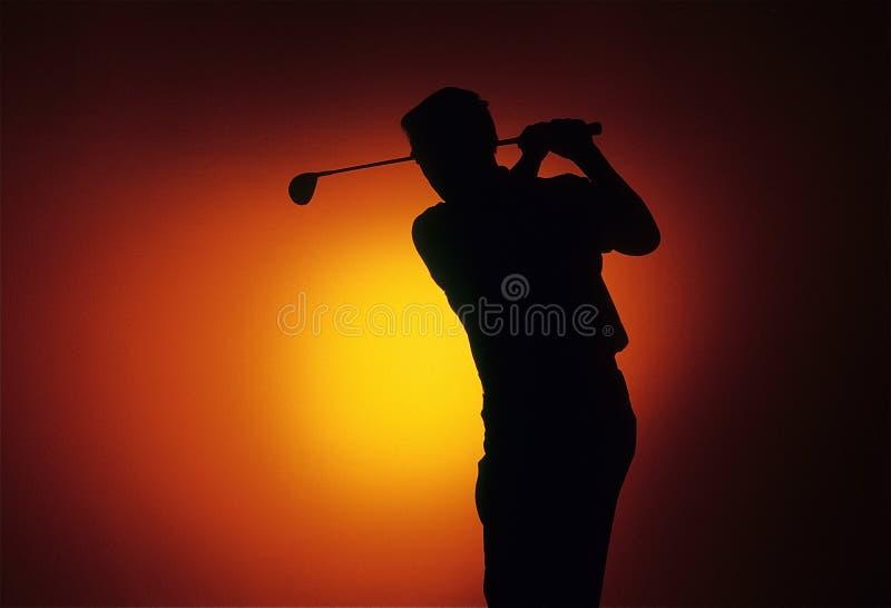 Golfista de la puesta del sol imagen de archivo