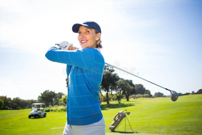 Golfista de la señora que junta con te apagado y que sonríe imagenes de archivo
