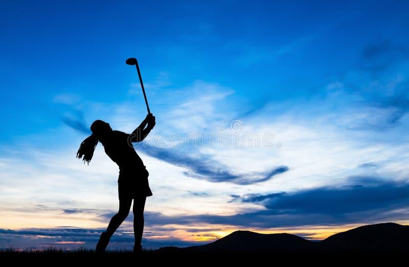 Golfista de la silueta que juega a golf en la puesta del sol hermosa fotografía de archivo