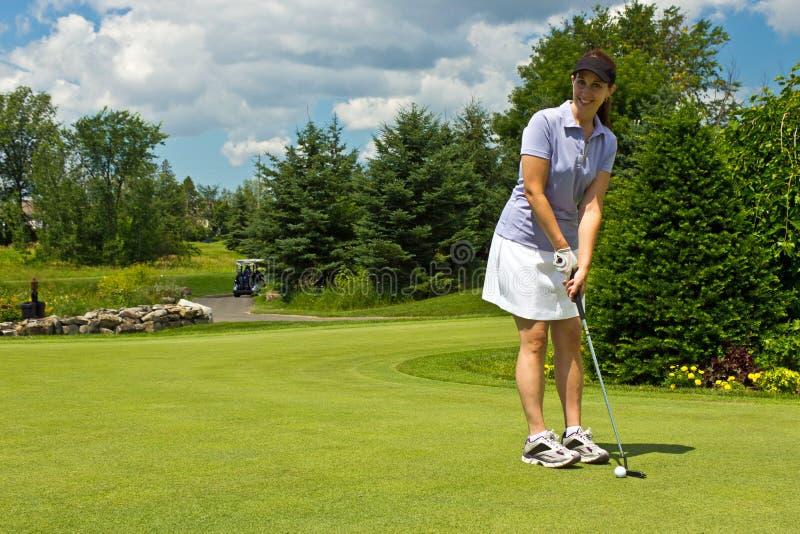 Golfista de sexo femenino que pone la pelota de golf en el verde foto de archivo