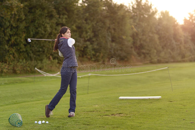 Golfista de sexo femenino que practica en un campo de prácticas fotografía de archivo