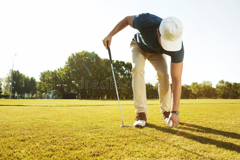 Golfista de sexo masculino joven que coloca la pelota de golf en una camiseta foto de archivo libre de regalías