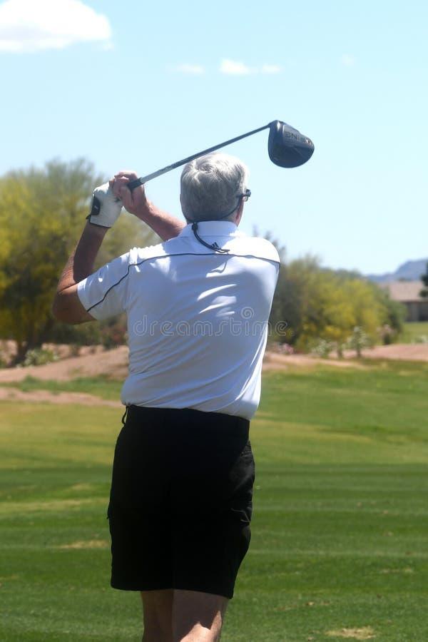 Golfista de sexo masculino que golpea una pelota de golf de una visi?n trasera fotografía de archivo libre de regalías
