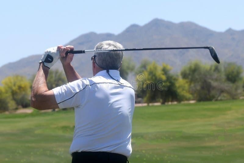 Golfista de sexo masculino que golpea una pelota de golf de una visi?n trasera imagen de archivo