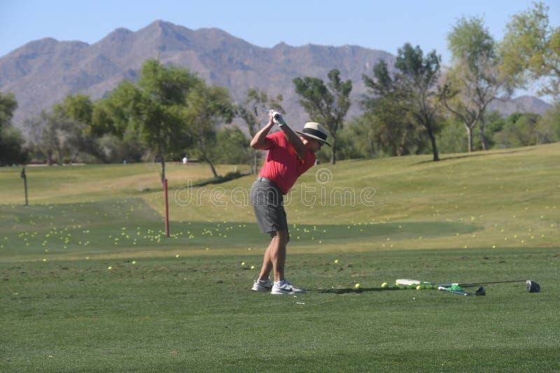 Golfista de sexo masculino que golpea una pelota de golf de una visi?n trasera foto de archivo libre de regalías