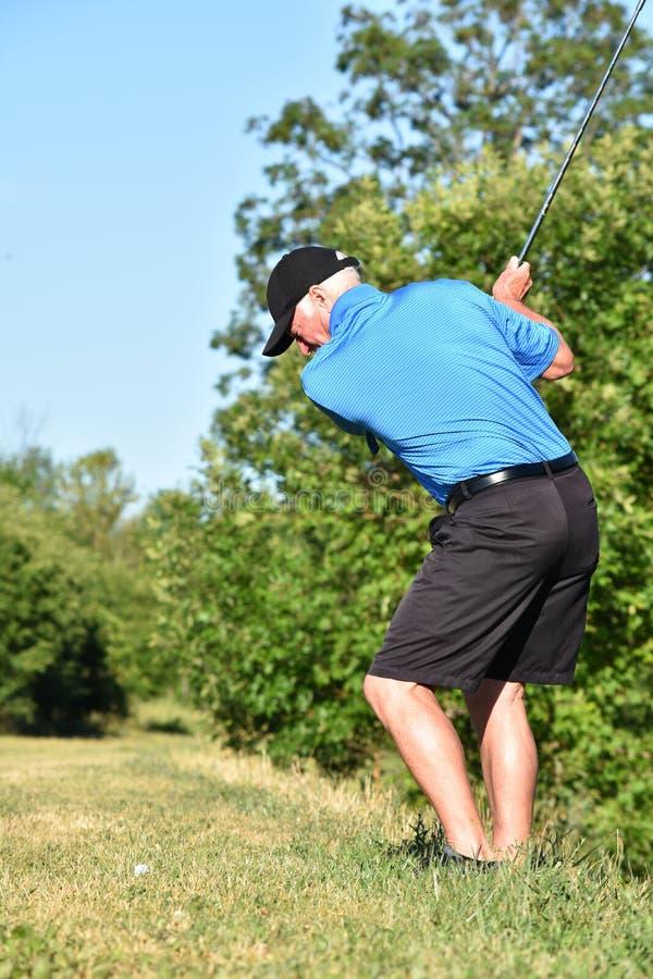 Golfista de sexo masculino que se resuelve con el oscilación del golf de Golf Club imagen de archivo libre de regalías