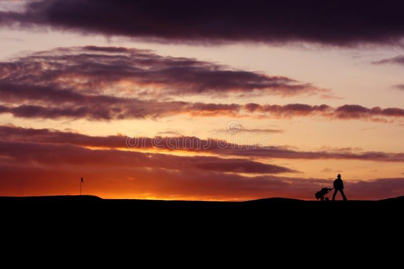 Golfista en la puesta del sol imágenes de archivo libres de regalías