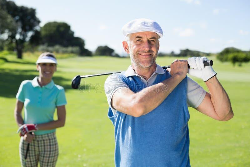 Golfista feliz que junta con te apagado con el socio detrás de él fotos de archivo libres de regalías