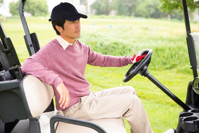 Golfista jedzie jego golfowy powozik fotografia stock