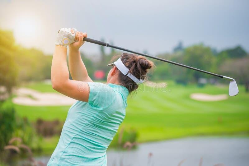 Golfista pcha pi?k? golfow? kijem golfowym od tr?jnik?w pude?ek przy polem golfowym w turniejowej gr? zdjęcie royalty free