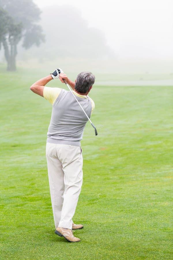 Golfista que balancea a su club en el curso fotografía de archivo libre de regalías