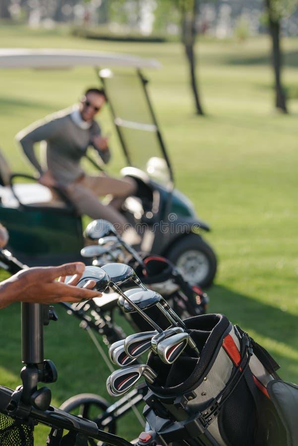 Golfista que elige al club de golf en campo de golf fotografía de archivo