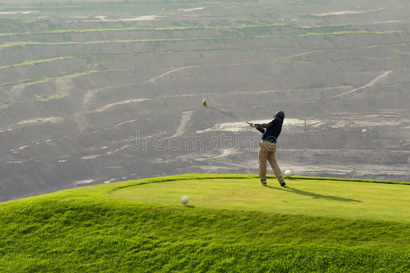Golfista que golpea la bola con el club en el campo de golf de Beatuiful fotos de archivo libres de regalías