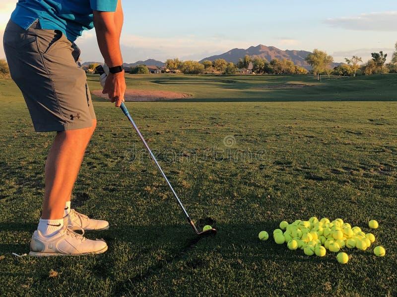 Golfista que golpea las pelotas de golf para la pr?ctica de una visi?n trasera imagen de archivo