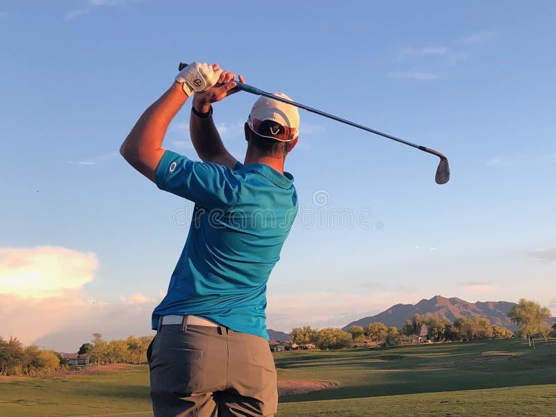 Golfista que golpea una pelota de golf de una visi?n trasera fotografía de archivo
