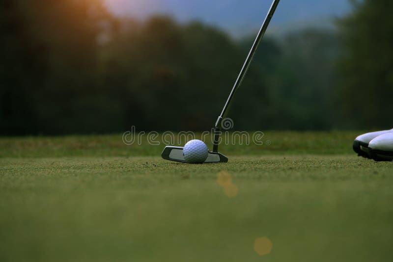 Golfista que pone la pelota de golf en el golf verde imagenes de archivo