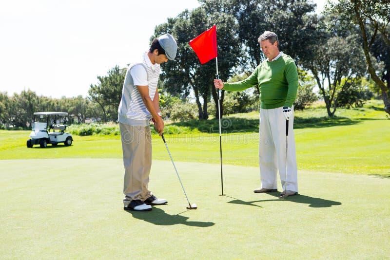 Golfista que sostiene la bandera del agujero para el amigo que pone la bola imágenes de archivo libres de regalías