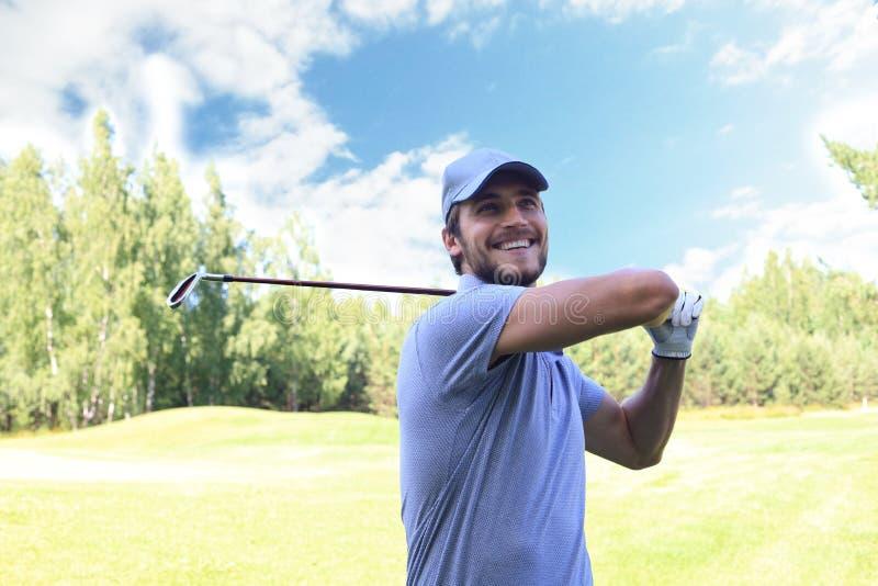 Golfista sonriente que golpea el tiro de golf con el club en curso mientras que el vacaciones de verano foto de archivo libre de regalías