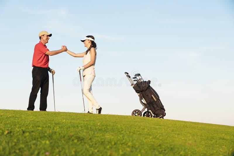 Golfista y caddie que juegan a golf fotografía de archivo libre de regalías