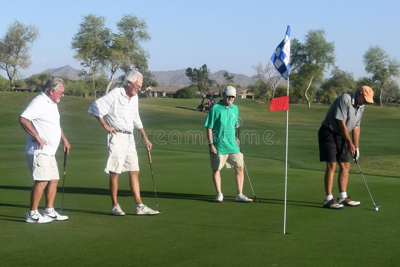 Golfistas de sexo masculino en putting green imagen de archivo
