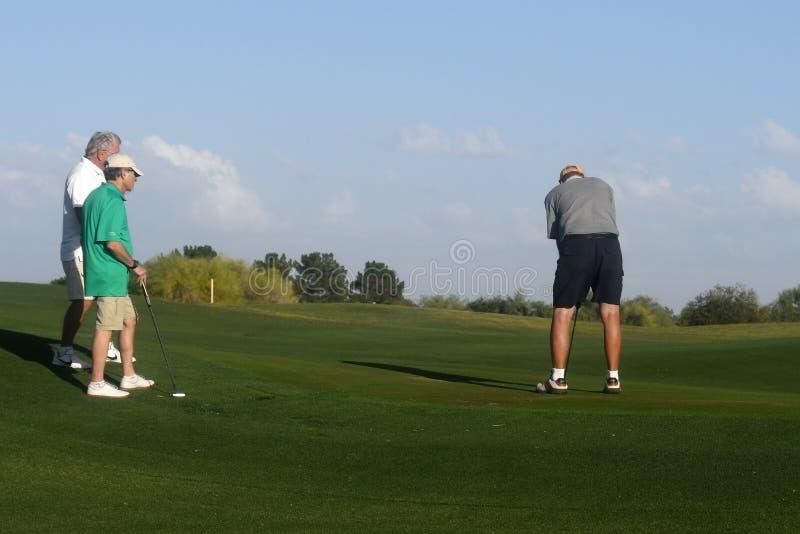 Golfistas de sexo masculino en putting green fotos de archivo libres de regalías