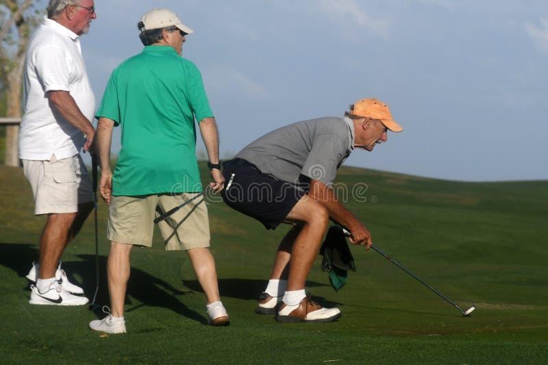 Golfistas de sexo masculino en putting green foto de archivo