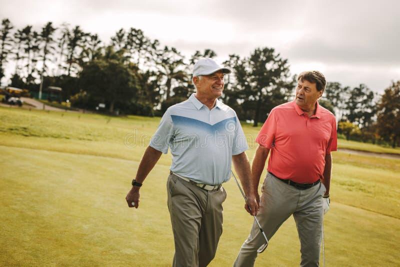 Golfistas mayores que caminan al agujero siguiente imágenes de archivo libres de regalías