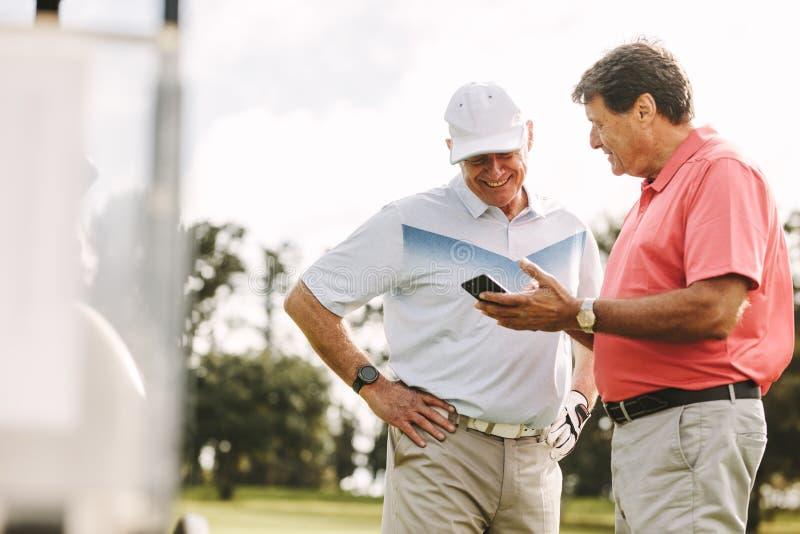Golfistas mayores que miran las cuentas en el teléfono después del juego imagen de archivo